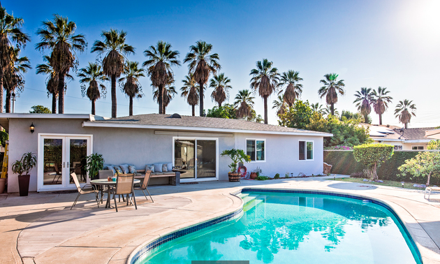 Charming Ranch-style pool home on a palm-tree lined street.